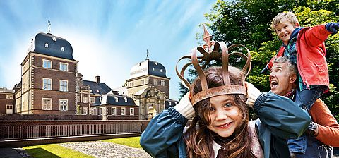 [Translate to Englisch:] Schloss, Mädchen mit Krone und ein Junge auf den Schultern seines Vaters